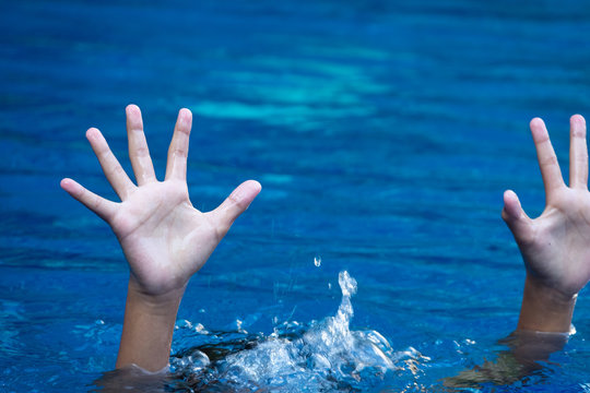 boy drowning in to the water and show up hands for help