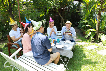 Happy multiethnic family giving surprise gift to caucasian grandfather on his happy birthday and he blowing out candles on homemade baked cake with happy face in backyard outdoor on sunny day