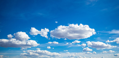 Blue sky background with clouds, sunny spring day