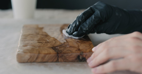 woodworker applying oil finish to olive wood board