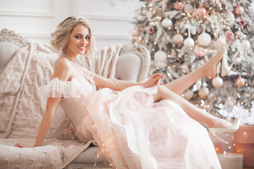 Young beautiful blond woman on christmas background full height. Attractive lady in pink gorgeous dress.