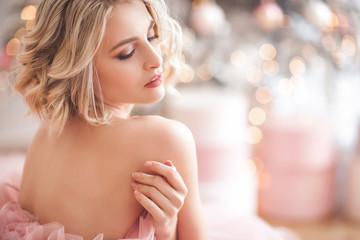 Fototapeta Beautiful young blond woman closeup. Lady on christmas background. Portrait of pretty female indoors. obraz
