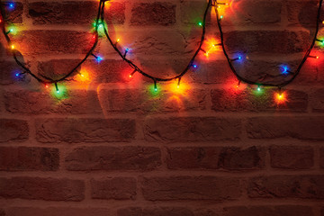 Bright colorful lights of garland on the brick wall