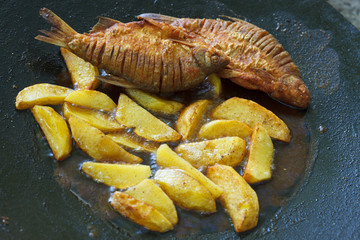 Frying carp fish and potatoes in deep fat. Fish and chips.
