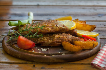 Fried Fish with potato on wooden board. Healthy food with omega 3 unsaturated fatty acid. Fish and chips.