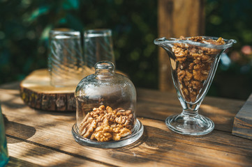 The walnuts in a glass jars on the wooden table in summer garden