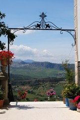Ornate iron gateway at Don Bosco house with views across the countryside towards the mountains, Ronda, Andalusia, Spain.