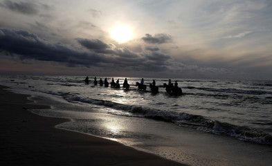 People ride horses in the sea at sunset at the Baltic Sea coast near Choczewo