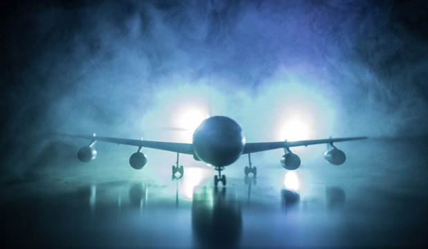 Artwork decoration. White passenger plane ready to taking off from airport runway. Silhouette of Aircraft during night time.