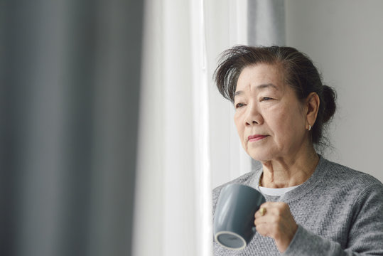 Asian senior woman drinking hot tea near window outdoor, lonely concept.