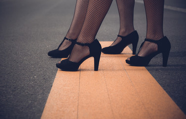 Two elegant woman wearing high heeled black shoes and sexy fishnet stockings modelling on wooden boards with foreground copy space in a low angle on their legs