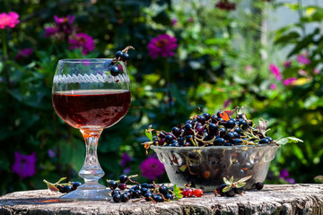 Blackcurrant wine with berries in avza glass from an old wooden table