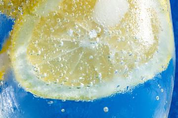 soda with lemon on blue macro