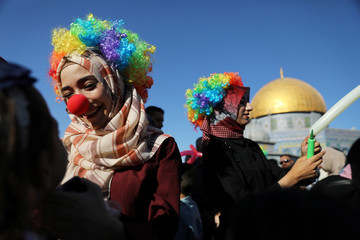 Women wear colourful wigs as the Dome of the Rock is seen in the background during celebrations marking the Muslim holiday of Eid al-Adha on the compound known to Muslims as Noble Sanctuary and to Jews as Temple Mount in Jerusalem's Old City