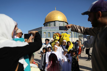 Children pose in front of the Dome of the Rock as their parents take photographs during celebrations marking the Muslim holiday of Eid al-Adha on the compound known to Muslims as Noble Sanctuary and to Jews as Temple Mount in Jerusalem's Old City