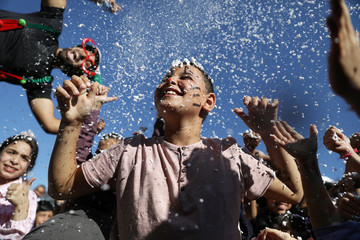 A youth smiles as foam covers him during celebrations marking the Muslim holiday of Eid al-Adha on the compound known to Muslims as Noble Sanctuary and to Jews as Temple Mount in Jerusalem's Old City