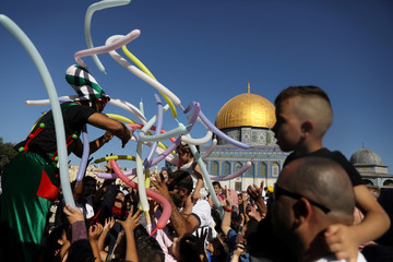 A man hands up balloons as the Dome of the Rock is seen in the background during celebrations marking the Muslim holiday of Eid al-Adha on the compound known to Muslims as Noble Sanctuary and to Jews as Temple Mount in Jerusalem's Old City