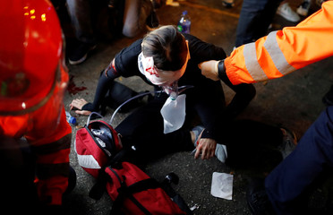 An injured young female medic receives medical assistance after being hit by a pellet round in the right eye during a demonstration in Tsim Sha Tsui neighbourhood in Hong Kong