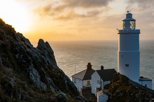 Wonderful lighthouse highlighted in warm light of sunrise with sharp rock in the picture