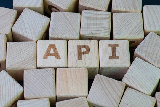 Application Programming Interface (API) middleware for applications to communicate with another concept, cube wooden block with alphabet combine the word API on black chalkboard background