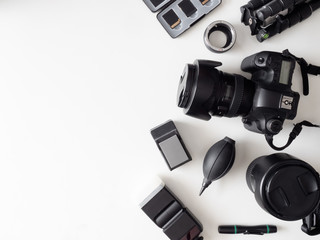 top view of work space photographer with digital camera, flash, cleaning kit, memory card, tripod and camera accessory on white table background