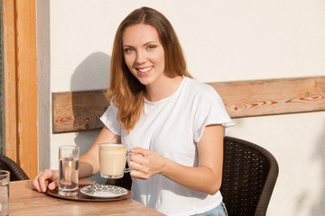 Beautiful young caucasian woman drink coffee in early morning