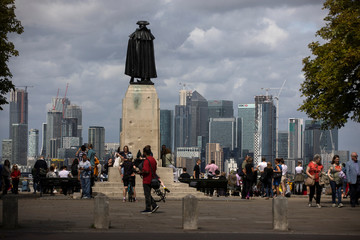 People look out onto the Canary Wharf financial district as they stand at a viewing area in Greenwich Park in London