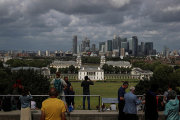 People take photos of the Canary Wharf financial district and the Greenwich Maritime Museum in London