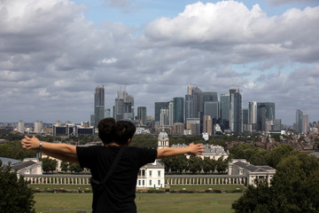A couple poses for a photograph with Canary Wharf financial district and the Greenwich Maritime Museum in London