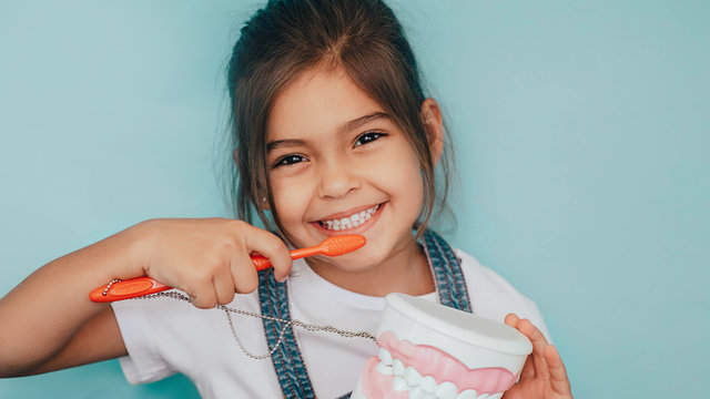 smiling mixed raced girl brushing teeth at blue background.