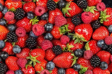 colorful tasty mix of wild forest berry fruits. Strawberry blueberry raspberry and blackberry. healthy eating nutrition vegan food concept background