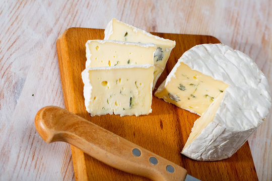 Image of slices of blue cheese with mold at wooden board