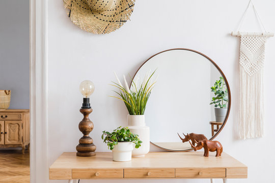 Sunny boho interiors of apartment with  mirror, dressing table, table lamp, flowers, plants, rattan hat, sculpture, macrame and design accessories. Stylish home decor of open space. Template.