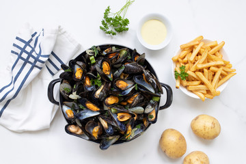 Belgian mussels with potato fries on while marble table overhead view