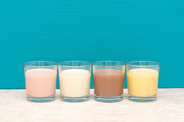 Flavoured milkshakes and fresh creamy milk in glass tumblers
