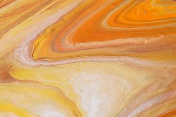 photography of abstract marbleized effect background. orange, gold, yellow and white creative colors. Beautiful paint.