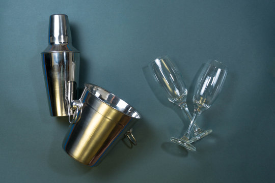 Silver bar utensils and their glasses on slate background