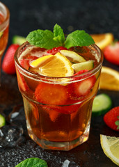 Refreshing Pimms Cocktail with Fruit and vegetables on rustic black table