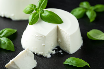 Fresh Ricotta cheese with basil leaf on black rustic table. selected focus