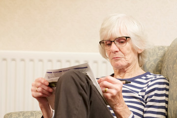Senior elderly woman keeping mind active doing a crossword puzzle to help anti-age old mind uk Wall mural