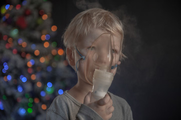 Caucasian blond boy inhales vapors containing medications to stop coughing. Medical procedures. Inhaler. Respiratory medicine. Bronchitis, asthmatic medical equipment. Xmas Eve, Christmas tree lights