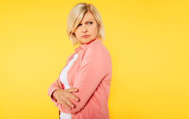 Angry blonde senior woman with crossed arms is posing over yellow background