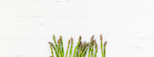 Fresh green asparagus on white wooden background