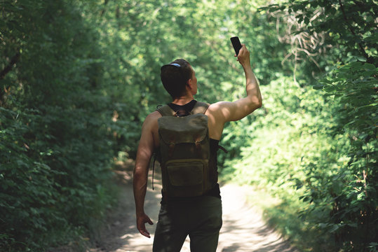 Man is stray in a forest and is trying to call mobile phone but no signal concept.