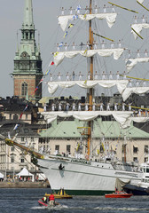 A Mexican three-masted barque is pushed towards the quay with its crew manning the yards in Stockholm