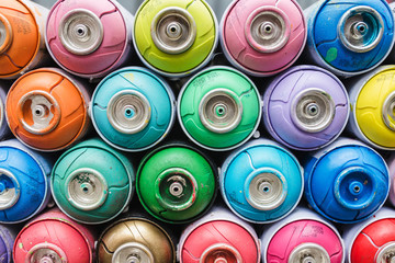 Graffiti artist tool - empty colored cans from under a spray of paint as a background or pattern