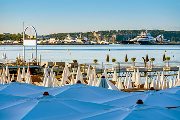 Sea bay with yachts boats and beach umbrella in Cannes