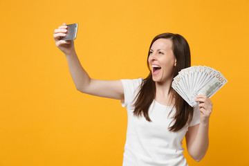 Joyful young woman in white clothes doing selfie shot on mobile phone, holding fan of cash money in dollar banknotes isolated on yellow orange background. People lifestyle concept. Mock up copy space.