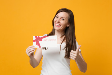 Portrait of smiling young woman in white casual clothes showing thumb up, holding gift certificate isolated on bright yellow orange background in studio. People lifestyle concept. Mock up copy space.