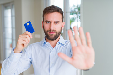 Handsome business man holding credit card with open hand doing stop sign with serious and confident...